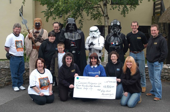 The Exewing Fundraisers presenting a cheque to Cancer Research UK
